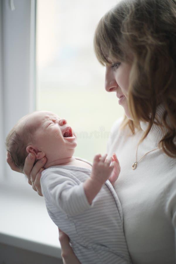 Jonge moeder met schreeuwende baby royalty-vrije stock foto