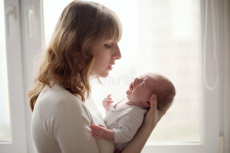 Jonge moeder met schreeuwende baby stock fotografie