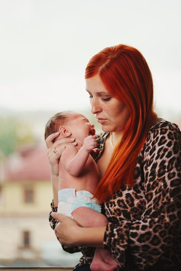 Jonge moeder met schreeuwende baby stock foto