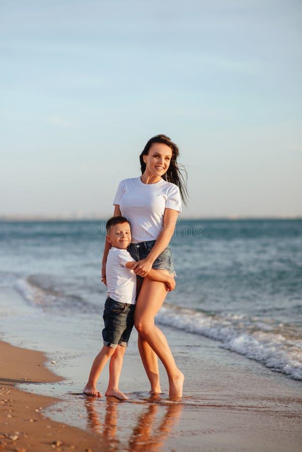 Jonge moeder met zoon in witte T-shirts stock foto's