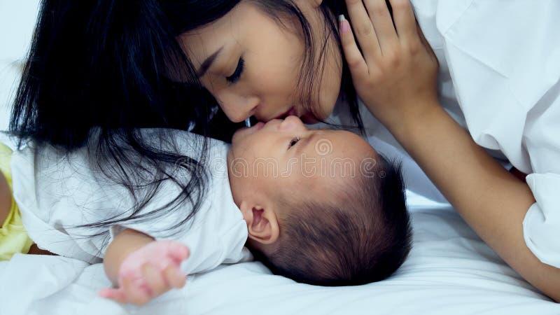 Jonge moeder snuggelt met haar baby op bed royalty-vrije stock foto