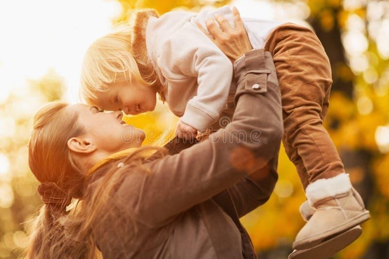 Jonge moeder toenemende baby omhoog stock foto