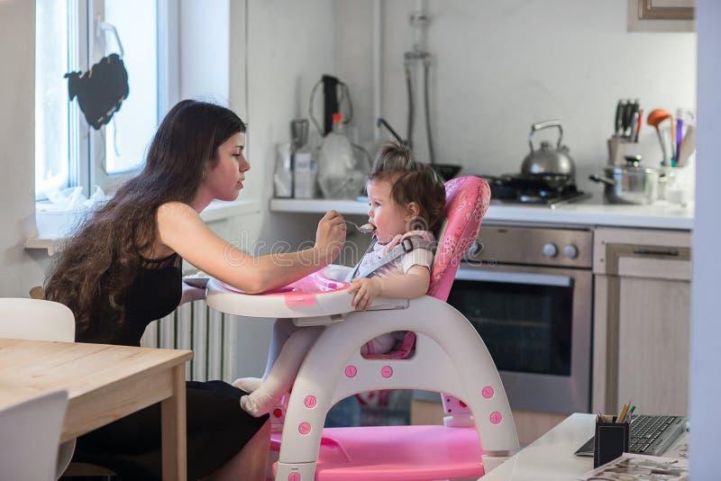 Jonge moeder voedende dochter royalty-vrije stock foto