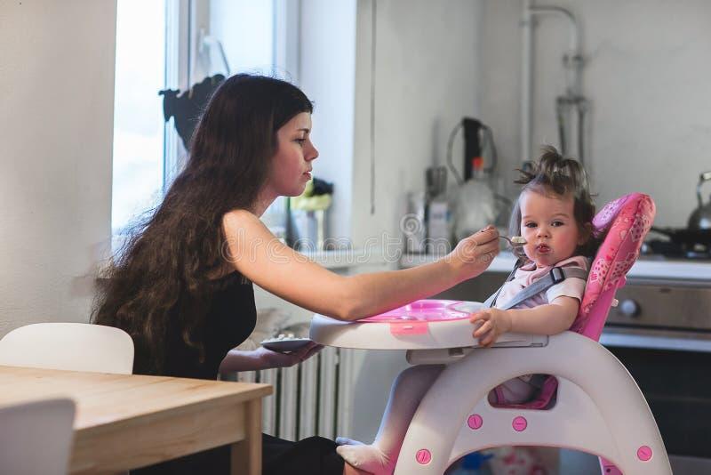 Jonge moeder voedende dochter stock afbeeldingen