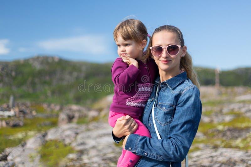 Jonge moeder in zonnebril met haar dochter bij de handen royalty-vrije stock foto's