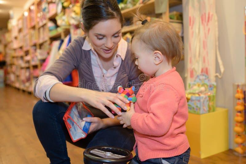 Jonge moederdochter die bij stuk speelgoed opslag winkelen royalty-vrije stock foto's