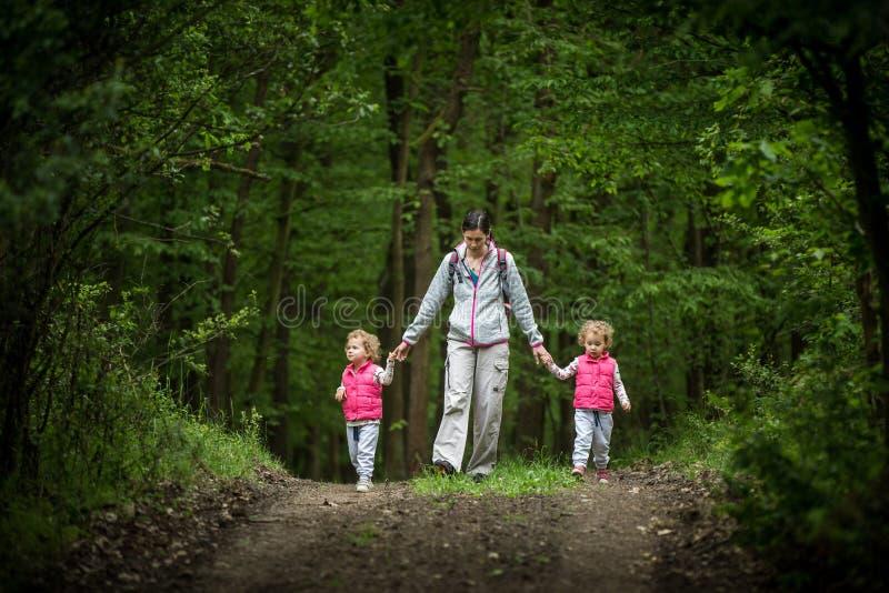 Jonge moedergang met identieke tweeling in hout, jonge mooie meisjes met blond krullend haar, vrijheid, vreugde, beweging, openlu stock afbeeldingen