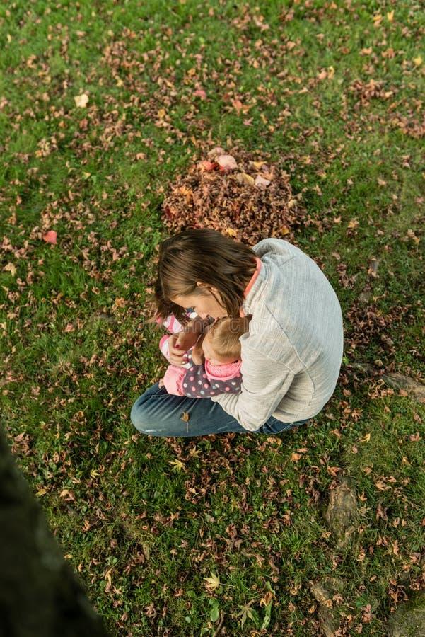 Jonge moederzitting in gras in een park terwijl het kussen van haar baby g royalty-vrije stock foto's