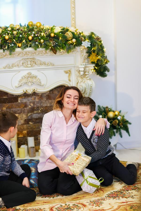Jonge moederzitting met zonen en giften dichtbij verfraaid open haard stock foto's