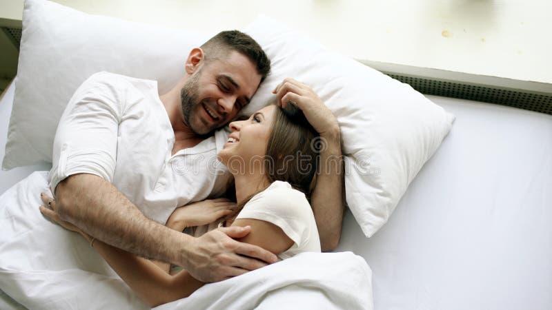 Jonge mooi en het houden van paarbespreking en omhelzing in bed terwijl ontwaken in de ochtend Hoogste mening van de aantrekkelij stock fotografie