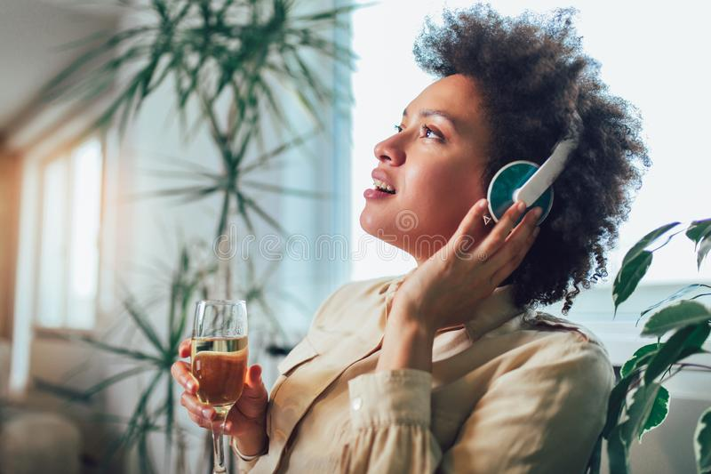 Jonge mooie Afrikaanse Amerikaanse vrouw die en aan muziek ontspannen luisteren die hoofdtelefoon met behulp van stock afbeelding