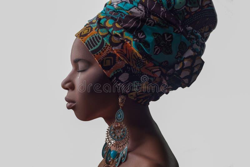 Jonge mooie Afrikaanse vrouw in in traditionele stijl met sjaal, oorringen schreeuwen, geïsoleerd op grijze achtergrond