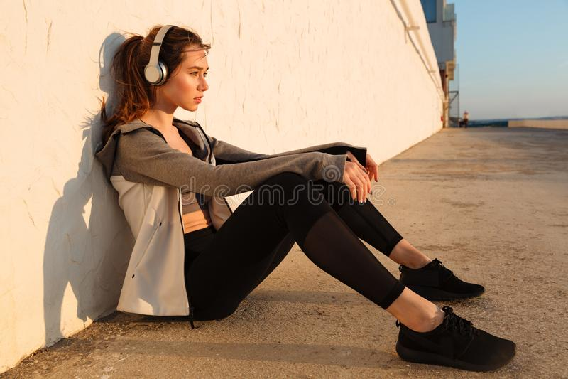 Jonge mooie agentvrouw die na looppas rusten, die aan muziek luisteren stock foto