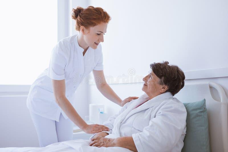 Jonge mooie arts en hogere patiënt bij het ziekenhuis royalty-vrije stock afbeelding