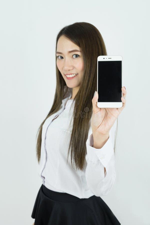 Jonge mooie Aziatische bedrijfsvrouw die, slimme telefoon van het Holdings de lege scherm op witte achtergrond glimlachen stock afbeeldingen