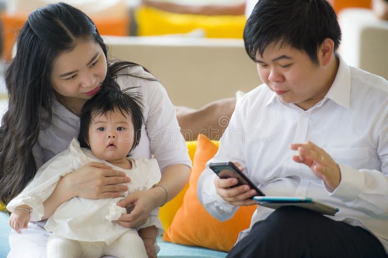 Jonge mooie Aziatische Chinese familiezitting bij moderne toevlucht met de werkende zaken van de werkverslaafdemens online met di stock foto's