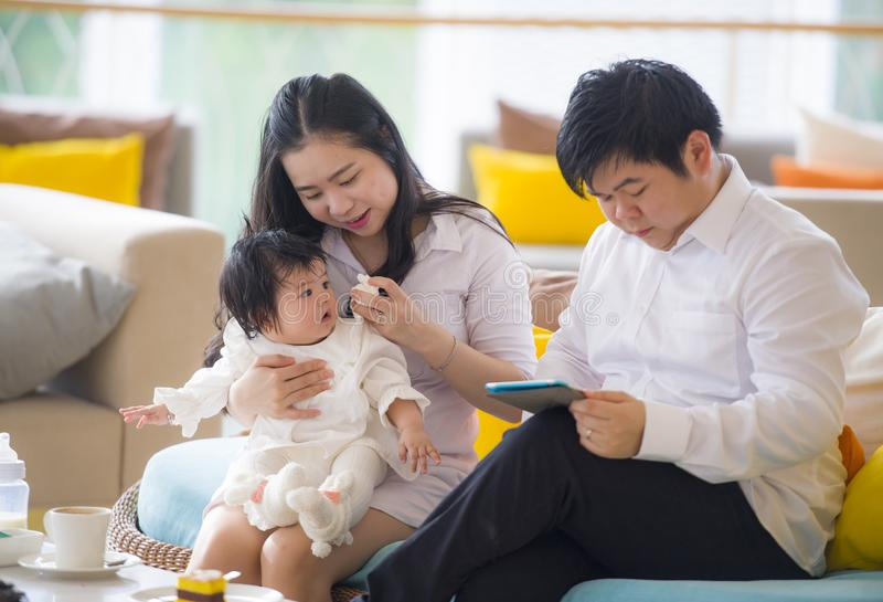 Jonge mooie Aziatische Chinese familiezitting bij moderne toevlucht met de werkende zaken van de werkverslaafdemens online met di stock fotografie