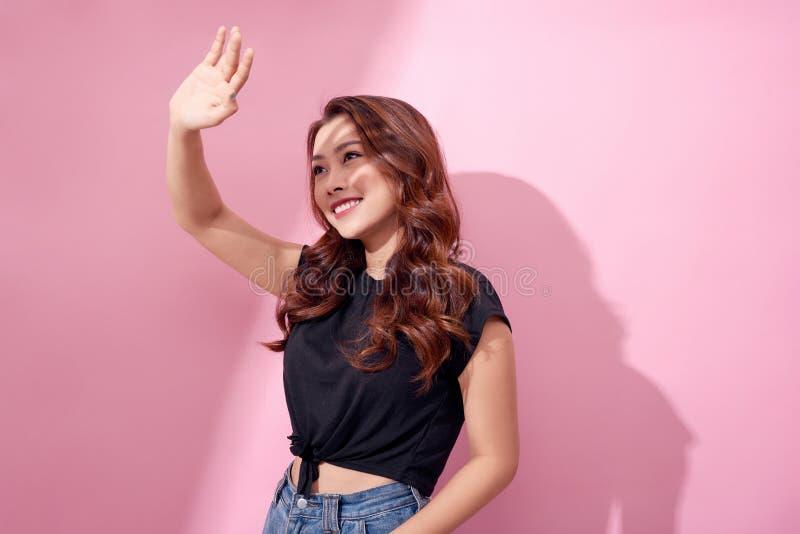Jonge mooie Aziatische die vrouw van zonneschijn over roze achtergrond wordt doen schrikken Concept voor de zorg van de de zomerh royalty-vrije stock fotografie