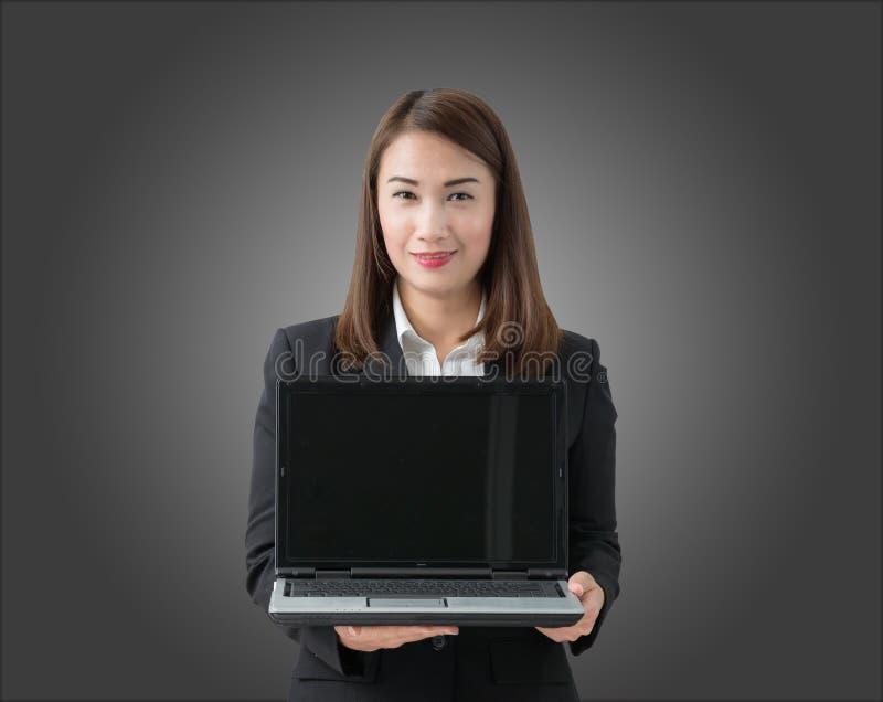 Jonge mooie Aziatische laptop van de bedrijfsvrouwenholding met leeg s royalty-vrije stock fotografie