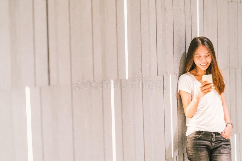 Jonge mooie Aziatische meisje of student die smartphone en het glimlachen gebruiken Moderne levensstijl, mobiele communicatietech royalty-vrije stock foto's