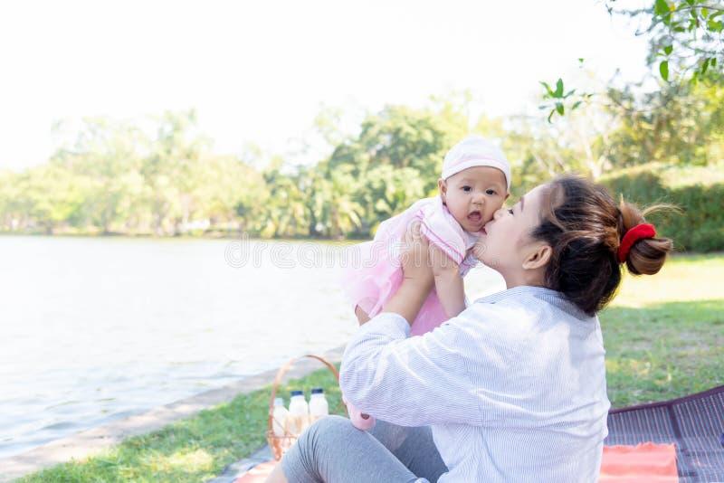 Jonge mooie Aziatische moeder die haar kussen weinig baby 4 maanden meisjes Familie; moeder en dochter die een vrije tijd hebben  royalty-vrije stock fotografie