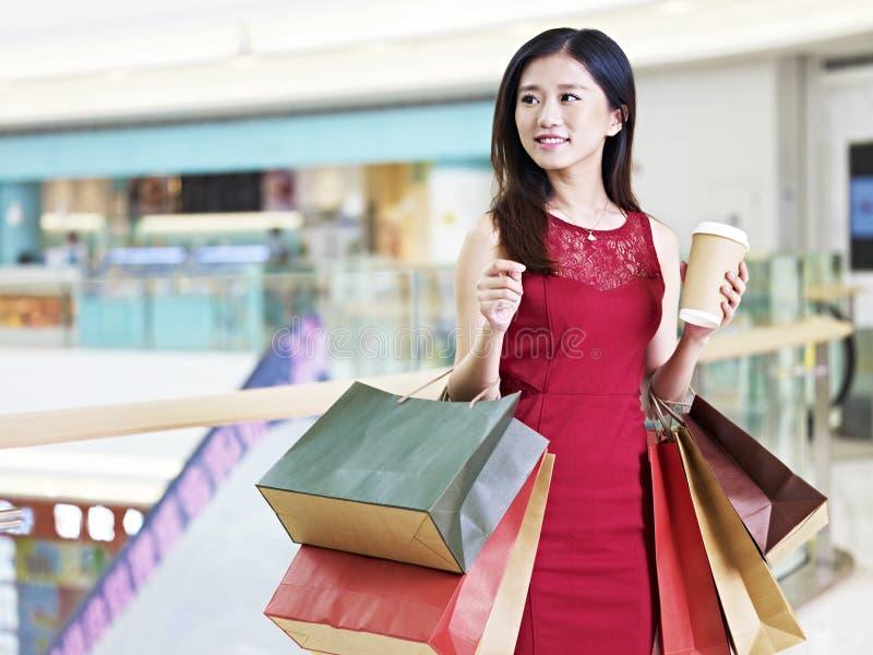 Jonge mooie Aziatische vrouw die in wandelgalerij winkelen royalty-vrije stock foto