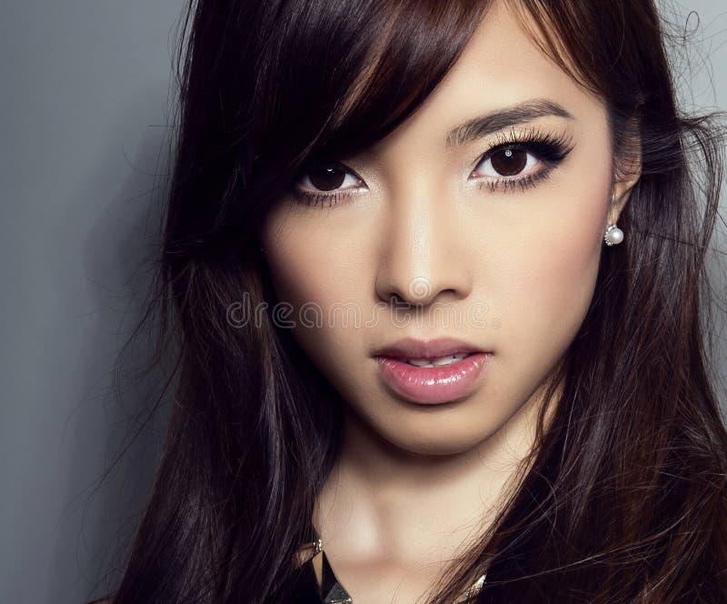 Jonge mooie Aziatische vrouw met onberispelijke huid en perfect samenstelling en bruine haar royalty-vrije stock foto's