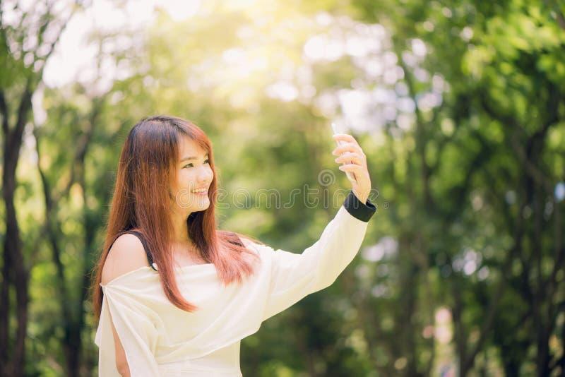 Jonge mooie Aziatische vrouwen met lang bruin haar die een selfie op haar telefoon in het park nemen stock afbeeldingen