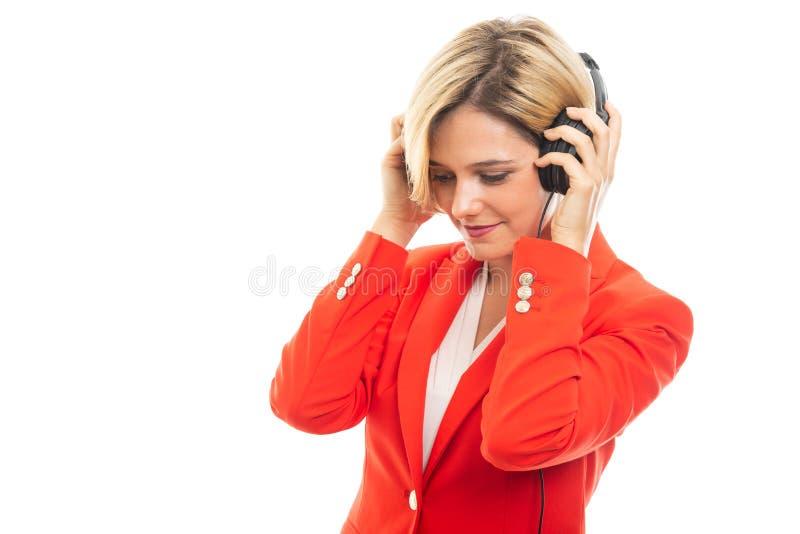 Jonge mooie bedrijfsvrouw die aan zwarte hoofdtelefoons luisteren royalty-vrije stock fotografie