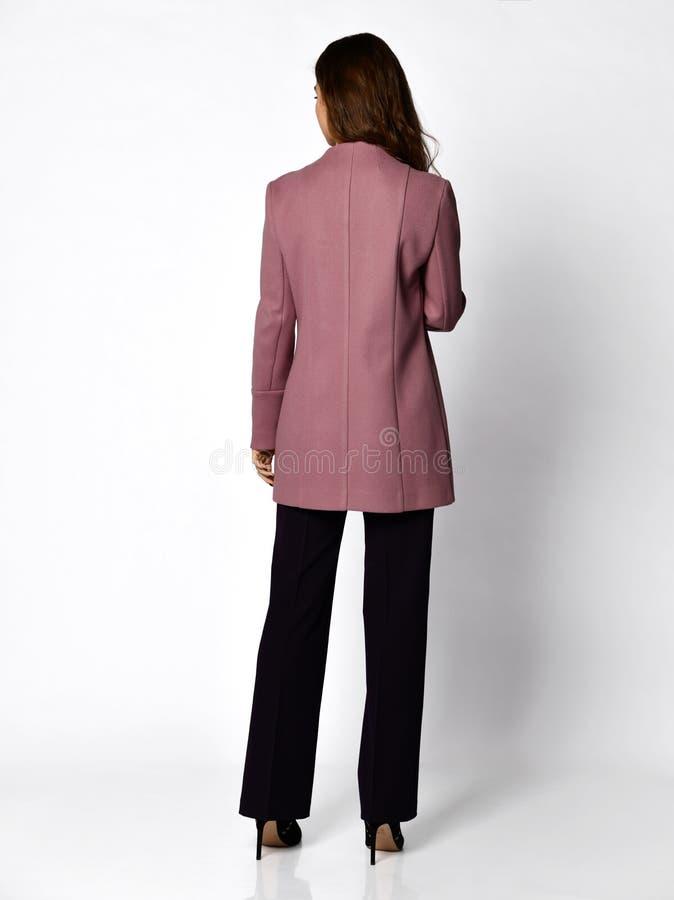 Jonge mooie bedrijfsvrouw die in het nieuwe purpere kostuum van de ontwerp toevallige lente op grijs lopen royalty-vrije stock afbeelding