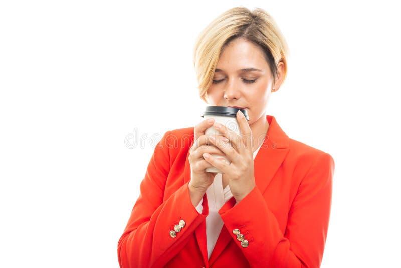 Jonge mooie bedrijfsvrouw die meeneemkoffiekop ruiken stock fotografie