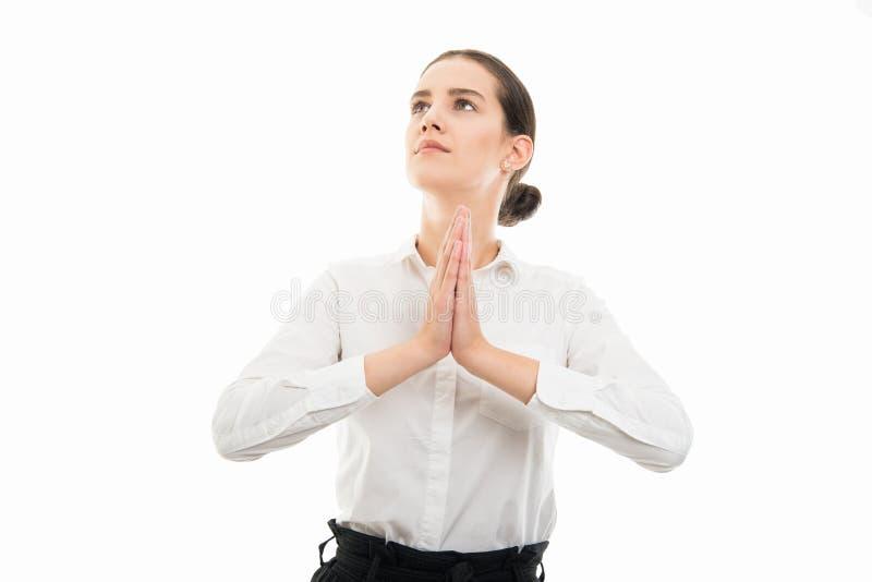 Jonge mooie bedrijfsvrouw die tonend het bidden gebaar kijken stock fotografie