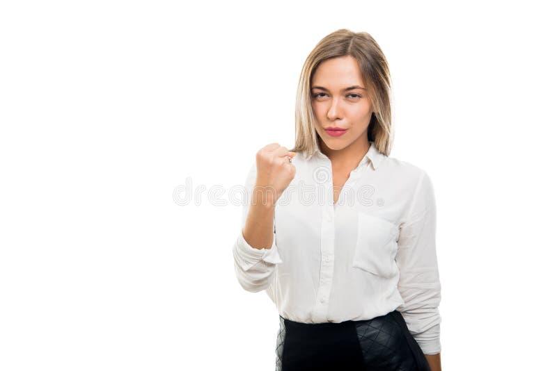 Jonge mooie bedrijfsvrouw die vuist als het vechten tonen stock foto