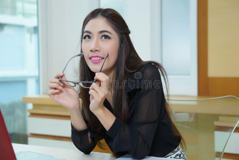 Jonge mooie bedrijfsvrouw met notitieboekje in het bureau stock foto's