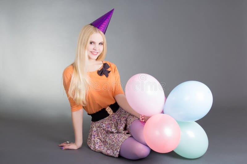 Jonge mooie blond met ballons die over grijs zitten royalty-vrije stock afbeeldingen