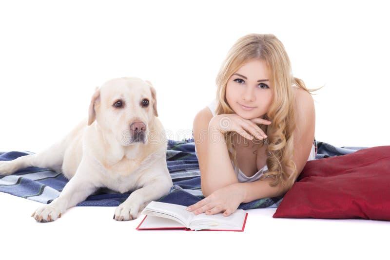 Jonge mooie blond in pyjama's die met boek en hond liggen isoleert stock afbeeldingen