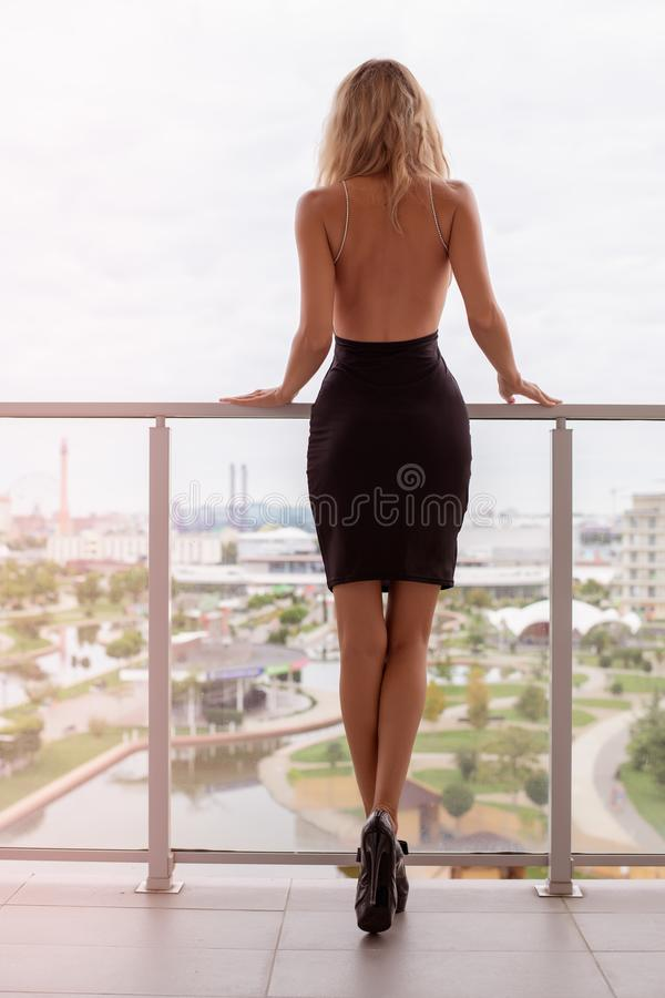 Jonge mooie blonde maniervrouw die zwarte kleding met open rug dragen stock afbeelding