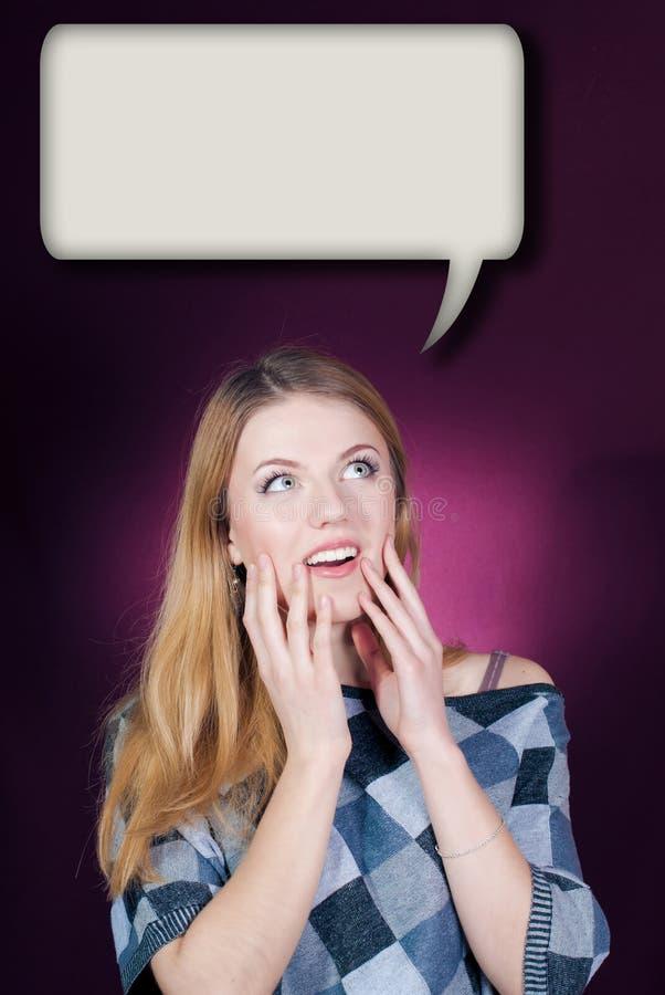 Jonge vrouw die omhoog in verbazing op dialoogdoos kijken