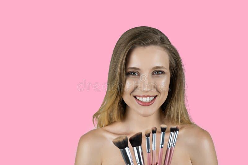 Jonge mooie blonde vrouw die roze borstels roze achtergrond houden royalty-vrije stock afbeelding
