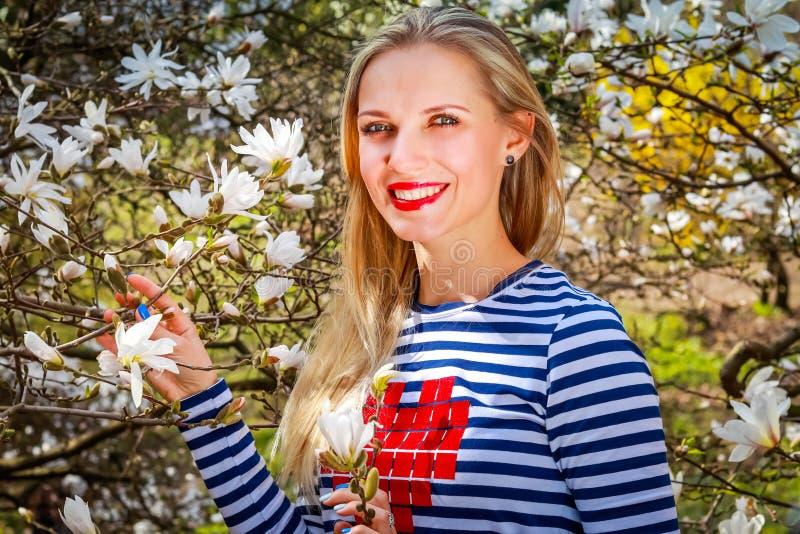 Jonge mooie blondevrouw in bloeiende tuin Magnolia royalty-vrije stock afbeelding