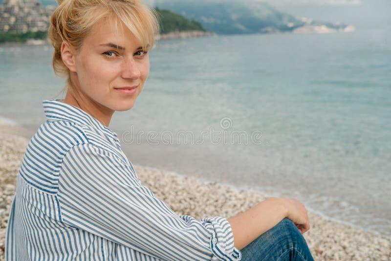 Jonge mooie blondevrouw in gestreept overhemd op overzeese achtergrond royalty-vrije stock foto's