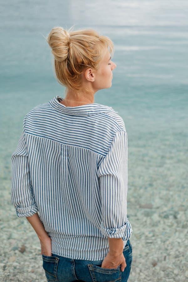Jonge mooie blondevrouw in gestreept overhemd op overzeese achtergrond royalty-vrije stock foto