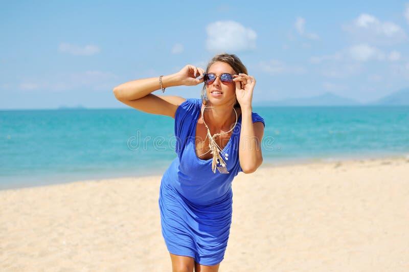 Jonge mooie blondevrouw in het blauwe kleding stellen in openlucht in su royalty-vrije stock fotografie