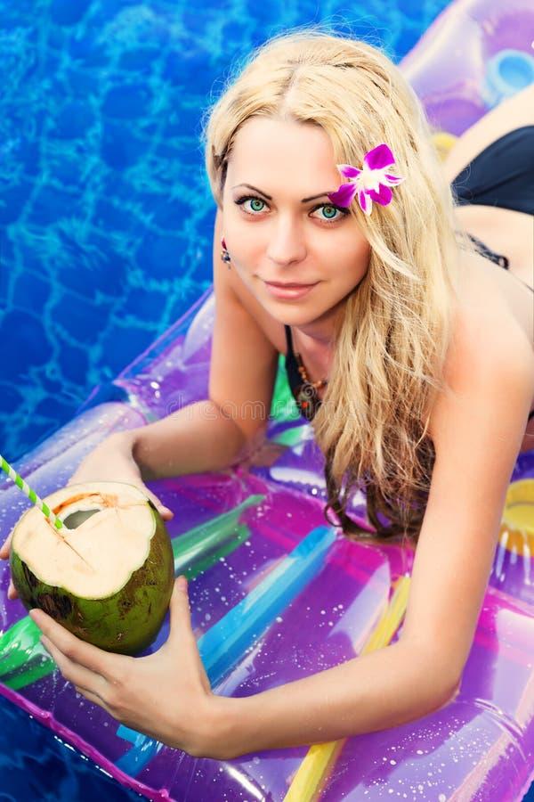 Jonge mooie blondevrouw op het zwembad van de luchtmatras royalty-vrije stock afbeeldingen