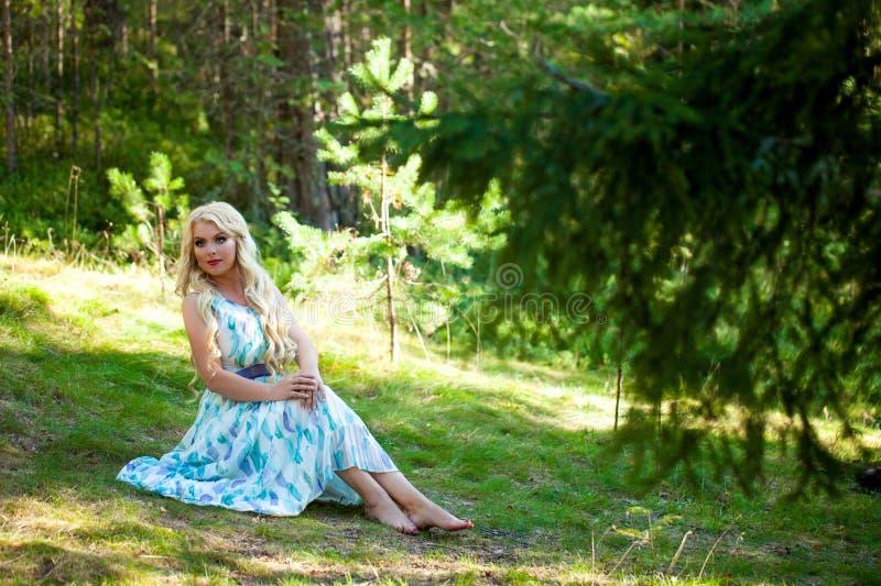 Jonge mooie blondevrouw in witte kleding met blauwe en groene bloemen die in bos stellen stock foto