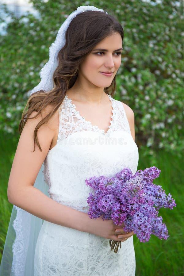 Jonge mooie bruid met boeket van lilac bloemen stock afbeeldingen