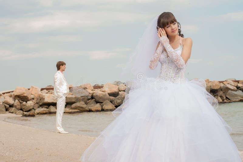 Jonge mooie bruid op het strand met zeeschelp royalty-vrije stock afbeelding