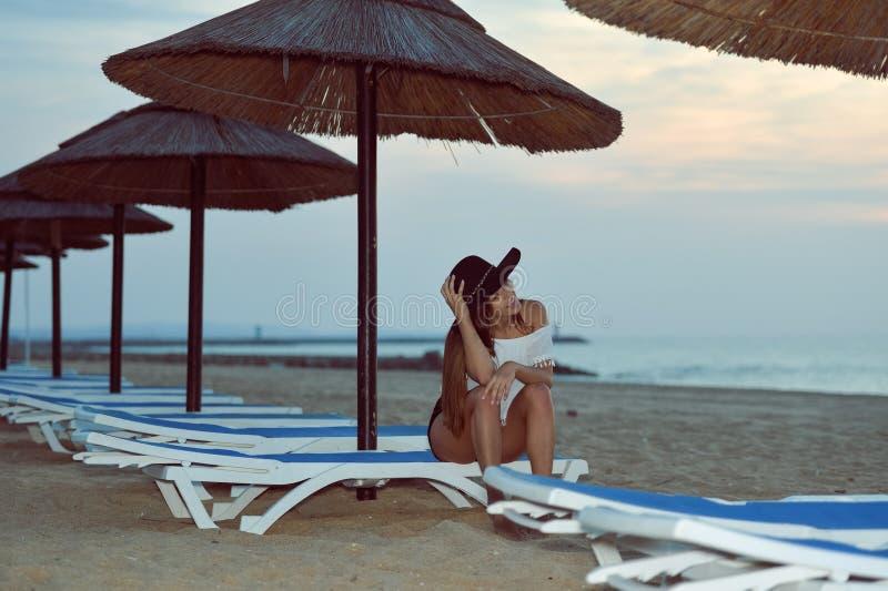 Jonge mooie dame bij strand het ontspannen in de avond dichtbij parasolzitkamer op de zomer in openlucht achtergrond stock afbeelding