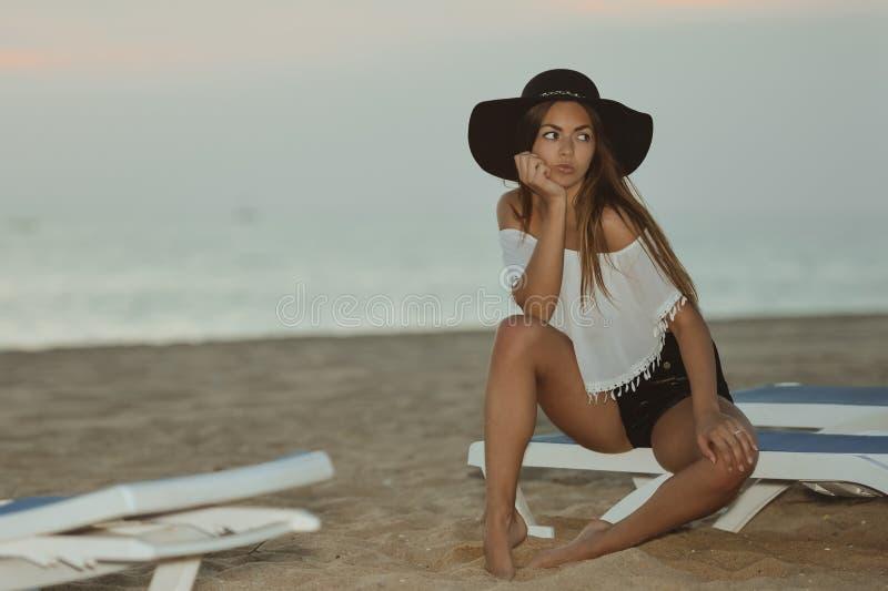 Jonge mooie dame bij strand het ontspannen in de avond op de zomer in openlucht achtergrond, vakantiereis stock afbeeldingen