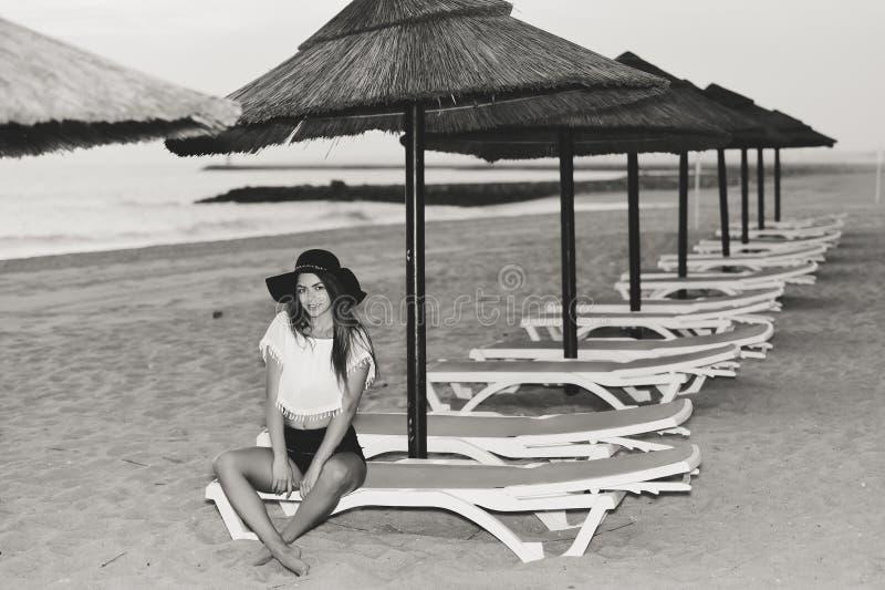 Jonge mooie dame bij strand het ontspannen in de avond op stoelzitkamer, de zomer in openlucht achtergrond stock foto